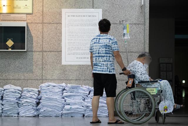 23일 서울 송파구 서울아산병원 로비에서 환자와 보호자들이 전공의들이 벗어놓은 의사 가운 위로 붙은 입장문을 바라보고 있다. 뉴스1