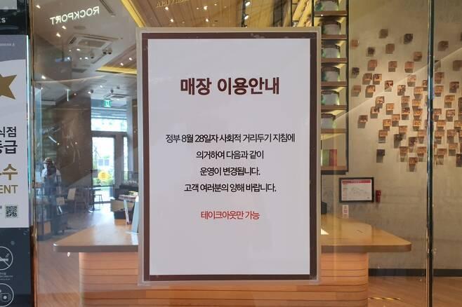 31일 낮 수도권 대형쇼핑몰에 입점한 프랜차이즈 카페가 붙여놓은 안내문. 내부 테이블은 모두 치운 상태로 테이크 아웃 고객만 받고 있었다. /사진=김남이 기자