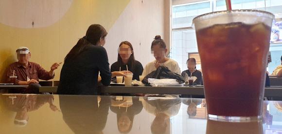 수도권에 사회적 거리두기 2.5단계가 시행되면서 프랜차이즈형 카페의 매장 내 취식이 불가능해진 30일 서울 중구의 한 햄버거 전문점에서 시민들이 음료와 햄버거 등을 먹고 있다. 음식점, 패스트푸드점 등은 오후 9시부터 실내 취식이 금지된다.박지환 기자 popocar@seoul.co.kr