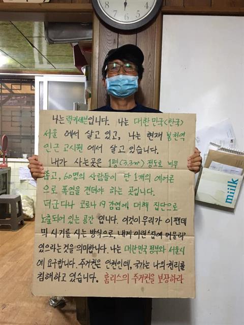 노숙인 활동가 럭키세븐이 서울의 한 고시원에서 '주거권을 보장하라'고 적은 피켓을 들고 있는 모습.빈곤사회연대 제공