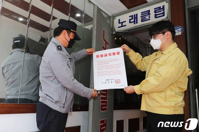 보건소 관계자와 경찰이 9일 관내 유흥업소에서 집합금지 명령서를 붙이고 있다.  (성동구청 제공) 2020.4.9/뉴스1