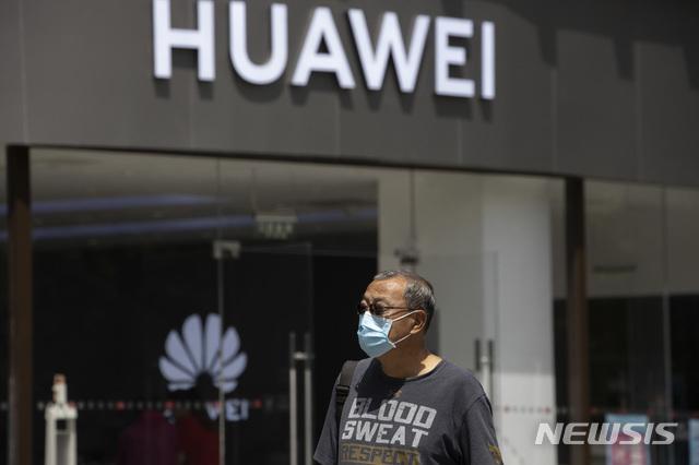 [베이징=AP/뉴시스]18일(현지시간) 중국 베이징에서 신종 코로나바이러스 감염증(코로나19)을 막기 위해 마스크를 쓴 한 남성이 화웨이 매장 앞을 지나가고 있다. 2020.05.18.
