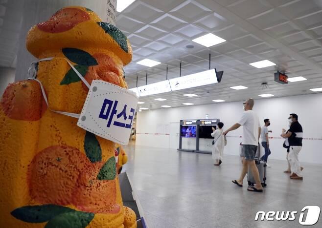 제주국제공항에서 마스크를 쓴 돌하르방 앞으로 관광객들이 지나가고 있다. 2020.8.30 /뉴스1 © News1 홍수영 기자