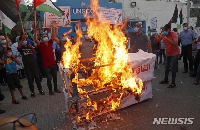 [가지지구=AP/뉴시스]팔레스타인인들이 15일(현지시간) 가자지구에 위치한 유엔 중동평화절차 특별조정관 사무실 앞에서 이스라엘과 아랍에미리트(UAE), 바레인간 평화협정 체결에 반대하는 사위를 벌이고 있다. 사진은 시위대가 3국 평화협정을 상징하는 모의 관을 불 태우는 모습. 2020.09.16