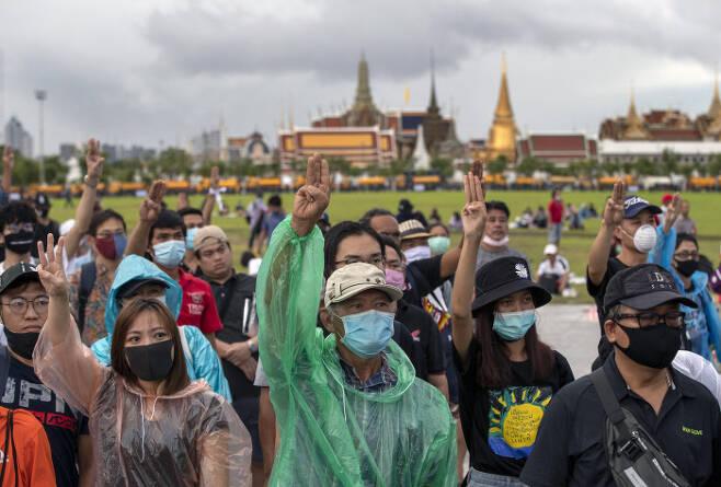 태국 민주화 시위대가 20일(현지시간) 방콕 사남 루엉 광장에서 시위를 상징하는 '세 손가락 수신호'를 하고 있다. 이 수신호는 쁘라윳 짠오차 총리 사퇴, 개헌, 반정부 인사 탄압 중지 등 '3대 요구'를 뜻한다. 시위대는 나아가 이날 시위에서 군주제 개혁을 촉구했다. 방콕|AP연합뉴스