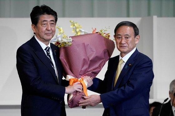 새 총리가 된 스가 요시히데가 아베 신조(왼쪽) 전 일본 총리에게 꽃다발을 선물하고 있다. 두 사람 모두 중국 진출 일본기업의 일본 복귀를 촉구한다. [로이터=연합뉴스]