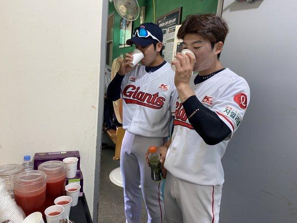 롯데 홍지훈 차혜성(왼쪽부터)이 건강음료를 마시며 목을 축이고 있다. 사진제공 | 롯데 자이언츠