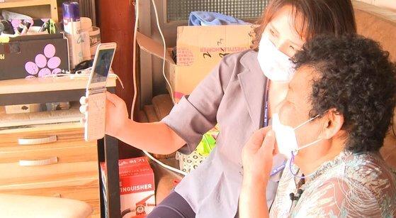 전남 완도군에 거주하는 어르신이 군청 공무원의 도움으로 딸과 영상통화를 하고 있다. 사진 완도군