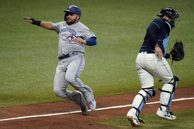 Toronto Blue Jays' Rowdy Tellez, left, scores behind Tampa Bay Rays catcher Mike Zunino on a sacrifice fly by Bo Bichette during the eighth inning of Game 1 of a wild card series playoff baseball game Tuesday, Sept. 29, 2020, in St. Petersburg, Fla. (AP Photo/Chris O'Meara)        <저작권자(c) 연합뉴스, 무단 전재-재배포 금지 >