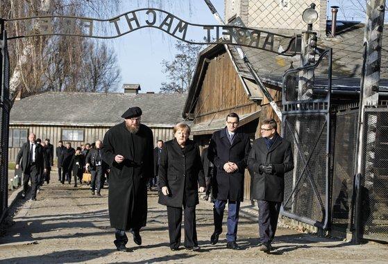 폴란드 아우슈비츠 비르케나우 박물관 연구센터 소장인 표트르 치빈스키 박사(맨 왼쪽)와 앙겔라 메르켈 독일 총리(왼쪽에서 두 번째)가 지난해 12월 6일 박물관 10주년을 맞아 수용소를 둘러보고 있다. [AP=연합뉴스]