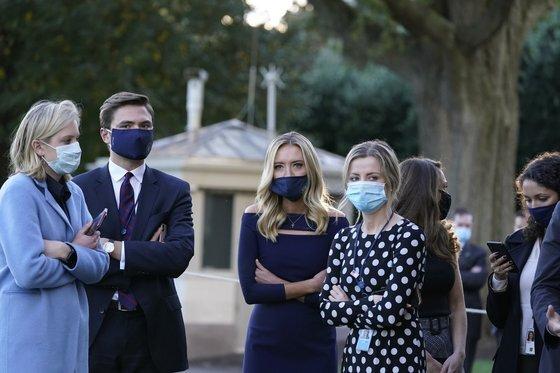 2일(현지시간) 워싱턴D.C 백악관에서 케일리 매커내니 백악관 대변인(가운데)을 포함한 백악관 직원들이 도널드 트럼프 대통령의 병원 이송 준비 과정을 지켜보고 있다.AP=연합뉴스]