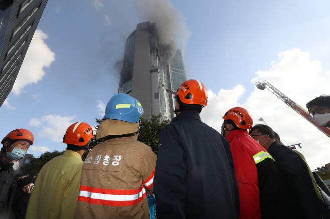15시간여 만에 진화 진영 행정안전부 장관(오른쪽에서 두번째)과 정문호 소방청장(세번째)이 9일 오전 연기가 치솟는 울산 남구 주상복합아파트 화재 현장을 살펴보고 있다. 전날 밤 발생한 불은 강풍을 타고 순식간에 33층 건물 전체를 덮쳤고(작은 사진) 15시간30분이 지나서야 완전히 꺼졌다. 연합뉴스