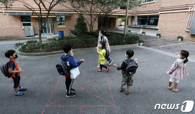 지난달 21일 경기 군포시 소재 한 초등학교에서 유치원생들이 등원하며 서로 인사를 나누고 있다./뉴스1 © News1
