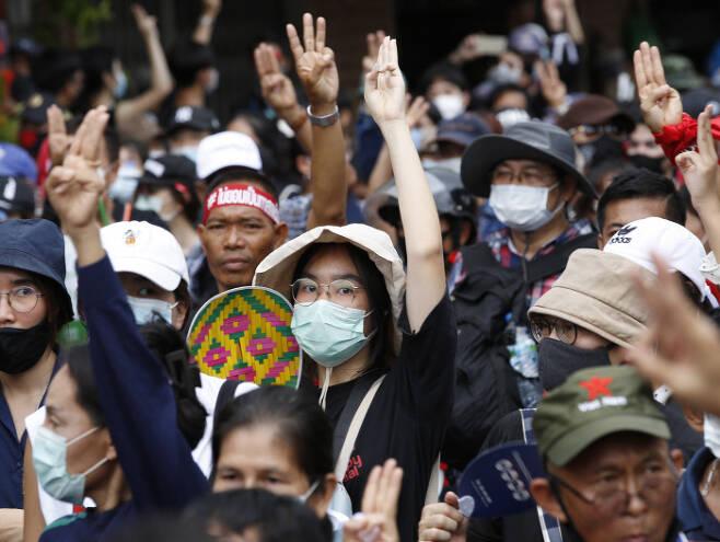 14일 방콕의 시위대가 정부청사 앞에서 군 출신 쁘라윤 짠오차 총리의 퇴진을 요구하며 불복종의 표시로 세 손가락을 들어올리고 있다. 방콕 | EPA연합뉴스