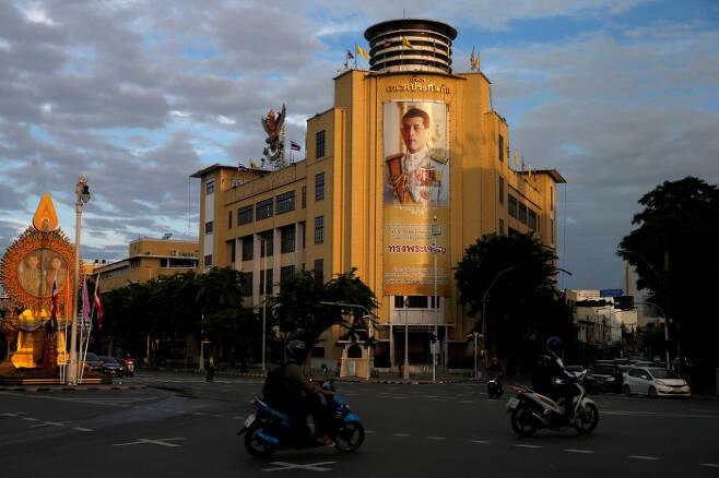 15일 방콕 도심에서 와치랄롱꼰 국왕의 사진이 걸려 있는 건물 앞으로 오토바이들이 지나가고 있다. 방콕 | 로이터연합뉴스