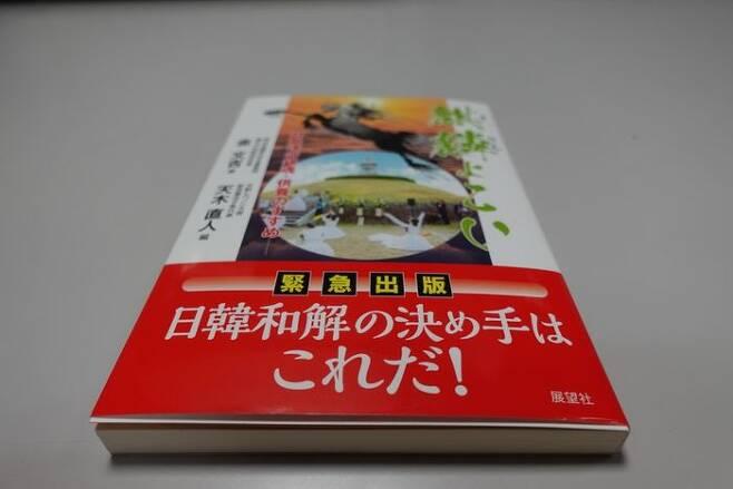"""일본에서 출판된 '기린이여 오라' 띠지에 적히 문장. """"일한화해의 결정타는 이것이다!"""""""