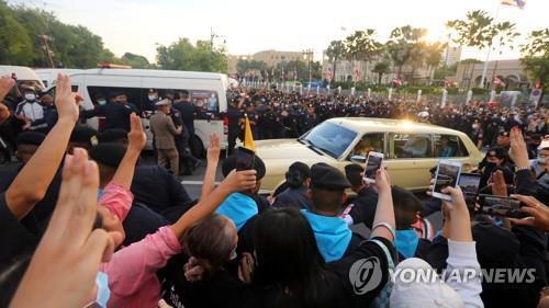수티다 왕비가 탄 차량을 향해 세 손가락 경례를 하는 시위대들. 2020.10.14 [로이터=연합뉴스. 재판매 및 DB 금지]