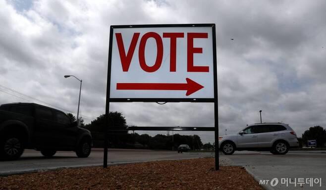 [플레이노=AP/뉴시스] 미국 보건 관련 단체는 24일(현지시간) 미국 대통령선거 투표소에서 신종 코로나바이러스 감염증(코로나19) 확산을 피하기 위해 '우편 투표'를 확대해야 한다고 주장했다. 사진은 지난달 29일 미국 텍사스주 플레이노 지역에 투표소를 알리는 간판에 설치된 모습. 2020.7.24.