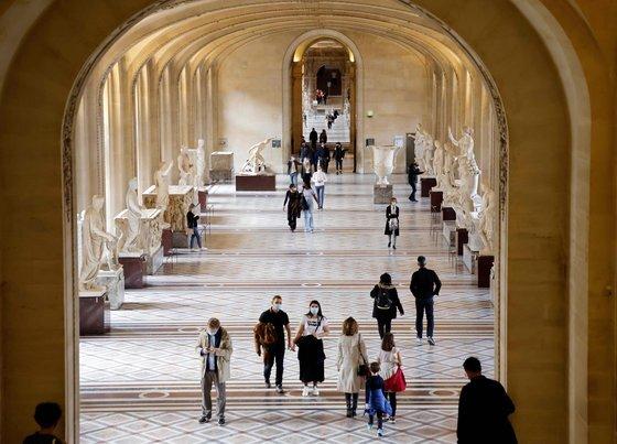 지난 14일 마스크를 착용한 관광객들이 프랑스 파리 루브르 박물관 회랑을 지나고 있다. 코로나19 확산으로 방문객 수가 크게 줄었다. AFP=연합뉴스