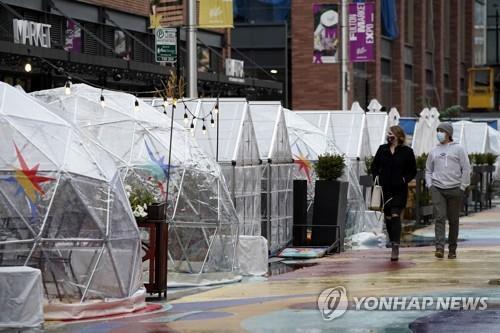 18일(현지시간) 비닐로 만들어진 실외 식사 천막이 설치된 미 시카고의 풀턴마켓 앞을 사람들이 지나가고 있다. [AP=연합뉴스]