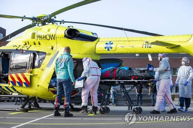 23일 네덜란드의 한 병원에서 의료진이 코로나19 환자를 헬리콥터를 이용해 이송하고 있다. [AP=연합뉴스]