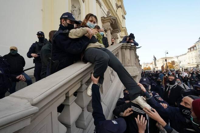 25일(현지시간) 폴란드 수도 바르샤바에 있는 한 성당에서 시위를 벌이던 여성을 경찰이 퇴거시키는 모습 [AFP=연합뉴스]