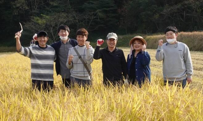 김동연 전 경제부총리(왼쪽 네번째)가 강선아 우리원 대표(다섯번째) 등 청년 농부들과 함께 추수 체험을 한 뒤 누렇게 익은 벼를 배경으로 화이팅을 외치고 있다. [정혁훈 기자]