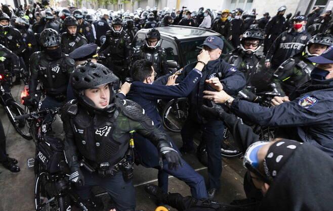 미국 뉴욕 경찰이 1일(현지시각) 트럼프 지지자들의 자동차 퍼레이드를 막으러 나온 시위대 중 한명을 체포하고 있다. 뉴욕/EPA 연합뉴스