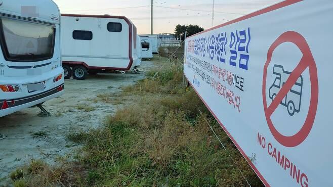 캠핑용 차량 주차장 장기 사용을 제한한다는 현수막이 설치된 강릉시 경포 호수공원에 캠핑카들이 주차돼 있다. [촬영 이해용]