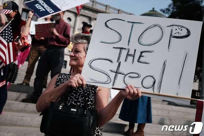 미국 펜실베니아주에서 한 트럼프 지지자가 '도둑질을 멈춰라'라고 적힌 팻말을 들고 있다. © AFP=뉴스1