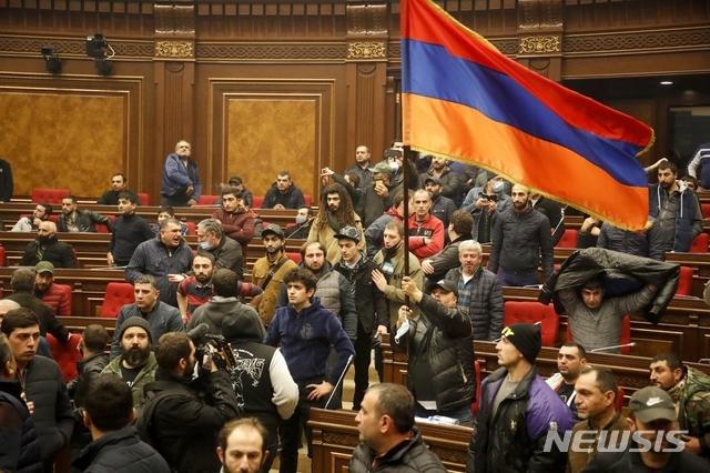 """[예레반=AP/뉴시스]10일(현지시간) 아르메니아 수도 예레반에서 나고르노-카라바흐 지역 분쟁 중단 합의에 반대하는 시민들이 정부 청사에 난입해 국기를 흔들며 시위하고 있다. 이날 아르메니안 정부가 나고르노-카라바흐 인근 일부 지역에 대한 통제권을 넘겨주는 등의 내용을 담은 분쟁 중단 합의를 발표하자 예레반 광장에 수천 명이 모여 """"우리 땅을 포기하지 않겠다""""라며 합의에 항의하고 있다. 2020.11.10."""