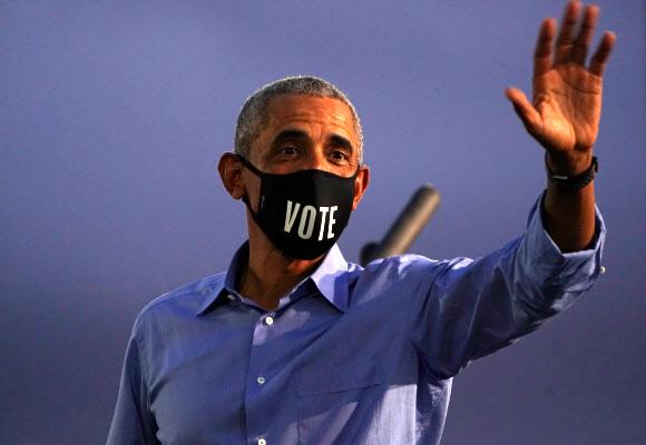 '투표하라'고 쓰인 마스크를 쓴 버락 오바마 전 미국 대통령이 21일(현지시간) 펜실베이니아주 필라델피아 유세에서 손을 흔들고 있다. 필라델피아 로이터 연합뉴스