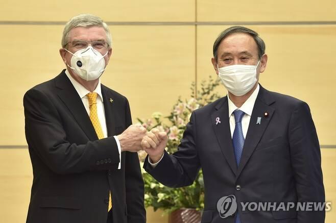바흐 IOC 위원장과 '주먹 인사' 나누는 스가 일본 총리 (도쿄 AP=연합뉴스) 스가 요시히데(오른쪽) 일본 총리가 16일 도쿄 총리관저에서 토마스 바흐 국제올림픽위원회(IOC) 위원장과 '주먹 인사'를 나누고 있다. 스가 총리와 바흐 위원장은 이날 회담에서 신종 코로나바이러스 감염증(코로나19) 탓에 연기된 도쿄올림픽과 패럴림픽의 내년 7월 개최를 재확인했다. sungok@yna.co.kr