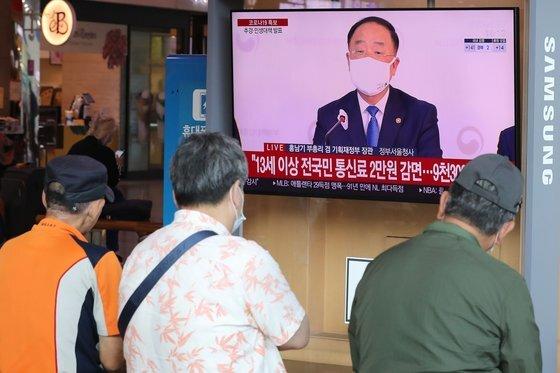 지난 9월 10일 서울 중구 서울역에서 시민들이 2차 긴급 재난지원금 지급 관련 뉴스를 지켜보고 있다. 뉴스1