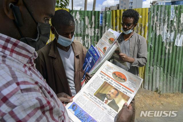 [아디스 아바바( 에티오피아)= AP/뉴시스] 지난 11월 7일 에티오피아 내전  뉴스를 신문에서 보고 있는 아디스 아바바 시민들.  아비 아흐메드 총리의 사진이 1면에 실려있다.