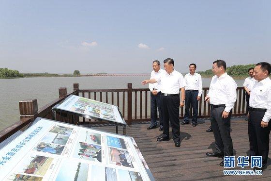 시진핑 중국 국가 주석이 수해 피해 지역을 시찰하고 있다. 뒷 배경으로 펼쳐진 강은 잔잔한 모습이다. 시 주석을 비롯해 함께 시찰하는 사람들도 구두를 신고 있다. [신화망]