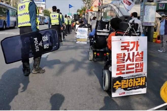 장애인 시민단체가 탈시설 국가 로드맵을 수립을 요구하며 서울시 종로구 도로에서 시위 행진을 하고 있다 (사진=서울장애인인권영화제 제공)