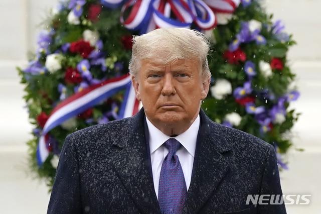 [알링턴=AP/뉴시스]도널드 트럼프 미국 대통령이 지난 11일 재향군인의 날을 맞아 버지니아주 알링턴에 있는 알링턴 국립묘지를 찾아 무명용사비를 참배한 후 비를 맞으며 돌아서고 있다. 2020.11.24.