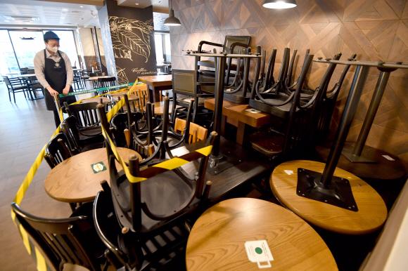 코로나19 확산을 막기 위한 사회적 거리두기 2단계 시행을 하루 앞둔 23일 서울의 한 프랜차이즈 커피 매장에서 직원이 테이블을 정리하고 있다. 박지환 기자 popocar@seoul.co.kr