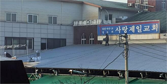 사랑제일교회 옥상에서 신도로 추정되는 인물이 인화물질을 옮기고 있는 모습 (사진=연합뉴스)
