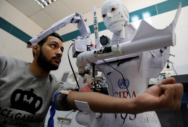 지난 18일(현지시간) 이집트 북부 탄타의 한 병원에서 간호사 로봇 시라-03이 채혈 검사를 하는 모습.(사진=로이터 연합뉴스)