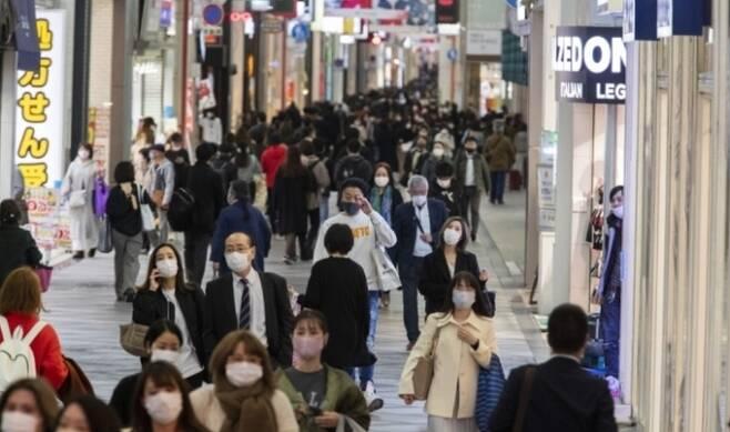 지난달 26일 마스크를 착용한 행인들이 오사카시의 한 쇼핑가를 지나가는 모습. AP/연합뉴스