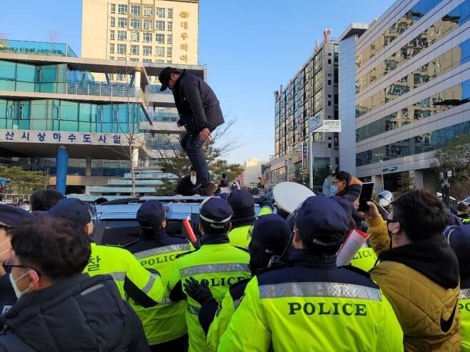 한 유튜버가 12일 안산보호관찰소에서 신상 등록을 마치고 빠져나오는 조두순이 탄 후송 차량 위에 올라타 발로 차 천장을 수차례 내리 찍고 있다. 안산 최영권 기자 story@seoul.co.kr