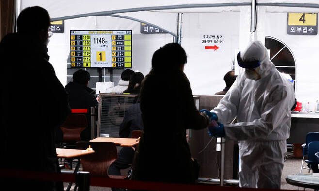 13일 서울 강남구 보건소 선별진료소를 찾은 시민들이 신종 코로나바이러스 감염증(코로나19) 검체 채취를 위해 문진표를 작성한 뒤 차례를 기다리고 있다. 연합뉴스