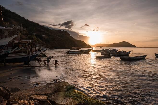 모래사장에서 보물을 찾고 있는 베네수엘라 해안 마을 주민들(사진=뉴욕타임스)