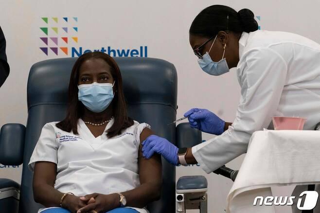 미국 뉴욕 유대인 의료센터 중환자실에서 근무하는 산드라 린제이 간호사가 14일(현지시간) 코로나19 백신을 맞고 있다. © AFP=뉴스1