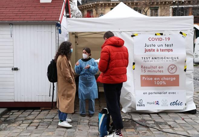 17일(현지 시각) 프랑스 파리의 한 거리에 세워진 임시 코로나 검사소에서 간호사가 사람들과 대화를 나누고 있다. /신화 연합뉴스