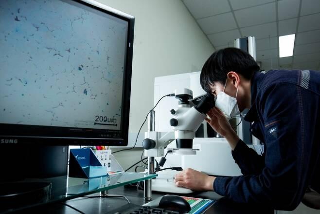 연구팀은 인터페이스에 양자역학을 적용해 금속 알갱이가 최대한 고르게 퍼질 수 있는 최적의 합금 조건을 찾았다. 연구원이 합금 표면의 구조를 들여다보고 있다. 남윤중 제공