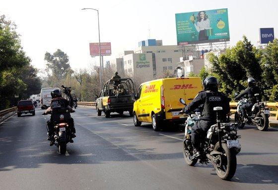 멕시코의 수도 멕시코시티에서 지난 23일 군인들과 셩찰이 무장 트럭과 오토바이를 타고 이날 이 나라에 처음으로 도착한 화아지바이오엔테크 백신의 운송 차량을 호위하고 있다. 로이터=연합뉴스