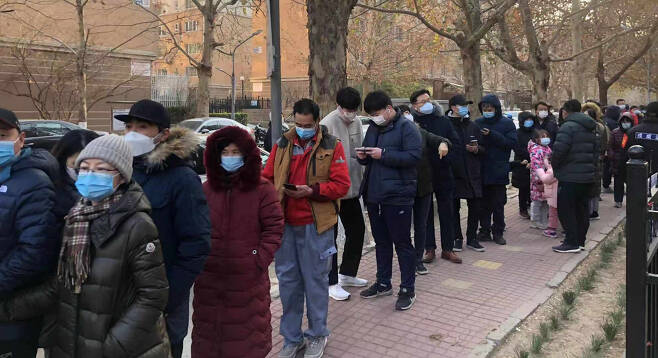 중국 수도 베이징과 동북부 랴오닝성에서 코로나19 확진자가 속출하고 있는 가운데 26일 베이징 차오양구 왕징의 한 아파트에서 코로나19 검사를 받으려 주민들이 줄을 서고 있다.[연합]